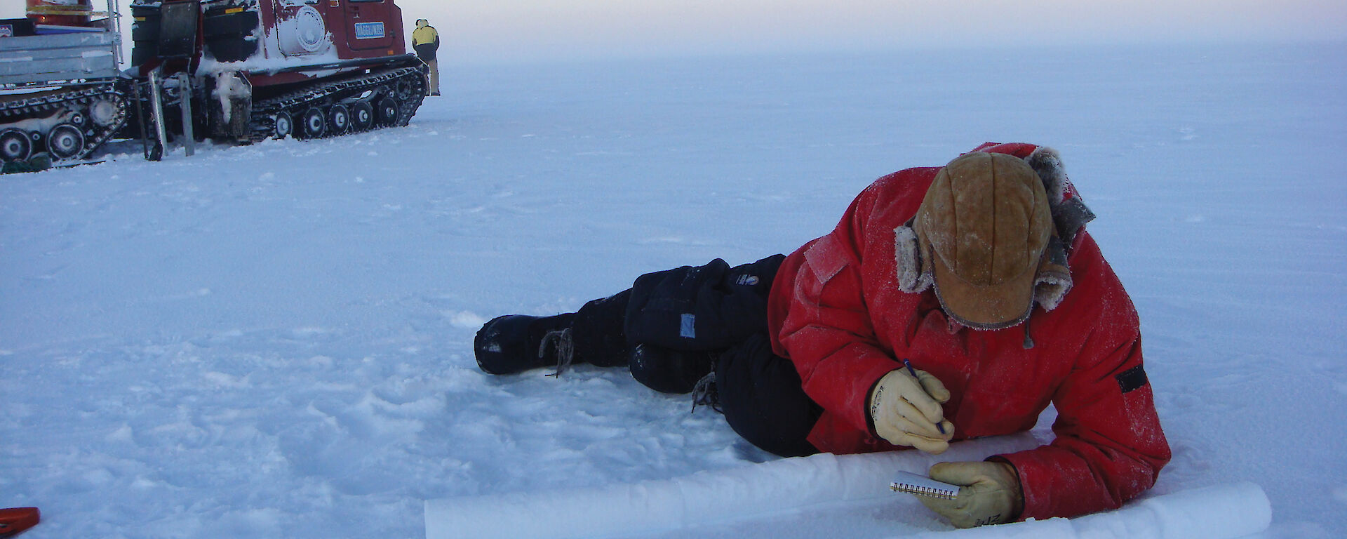 Ice core chemist lying on ice, cataloguing ice cores