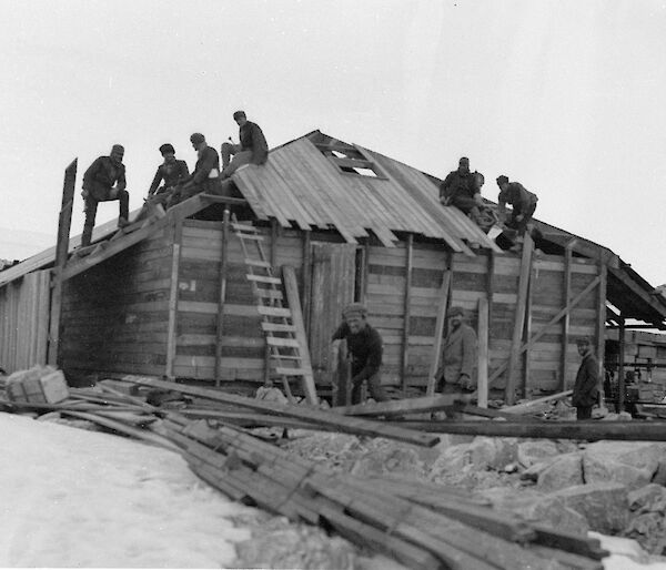 Mawson's huts construction with workers on the roof and around the hut