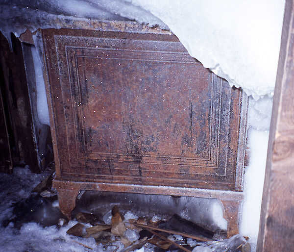 One side of the stove in Mawson's main hut is visible through ice and other detritus, when uncovered in 2002.