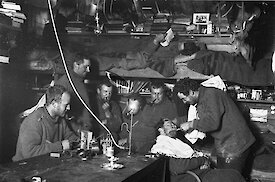 Frank Hurley trims John Hunter's beard. Other figures (L-R): Bage, Stillwell, McLean, Madigan, Hodgeman and Laseron on the bunk.