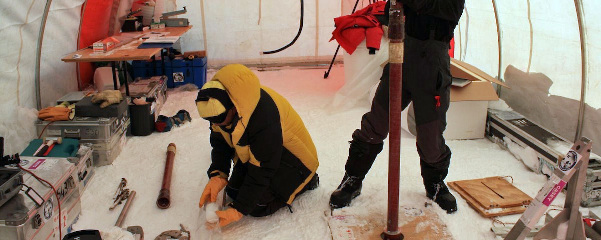 2 ice core scientists working in a drill tent in Antarctica