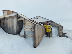 David Ellyard stands outside Mawson's Main Hut, surrounded by snow and ice.