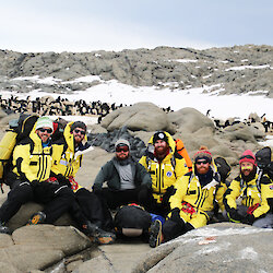 Group of expeditioners in yellow field jackets pose for camera on rocky terrain with penguin colony behind.