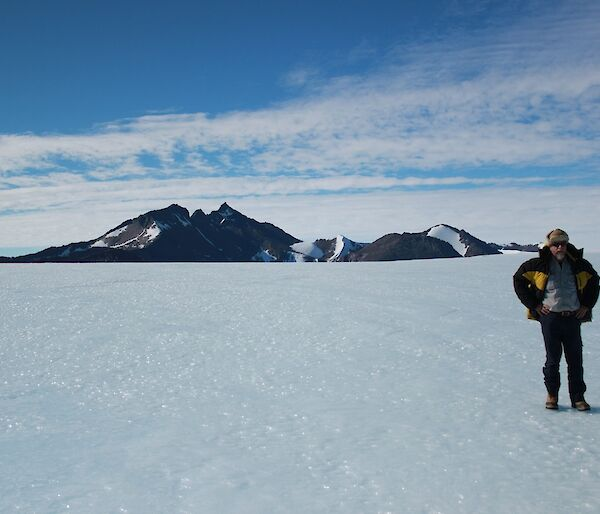 Expeditioner Lloyd standing on the ice plateau with Mt. Henderson in the background