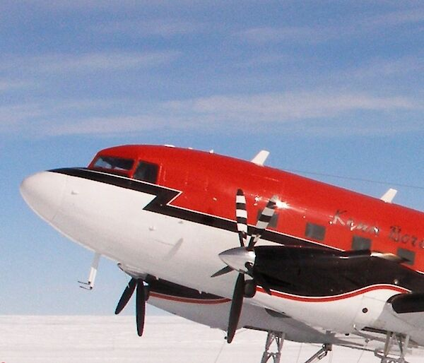 Red and white Basler modified DC-3 parked on its skis
