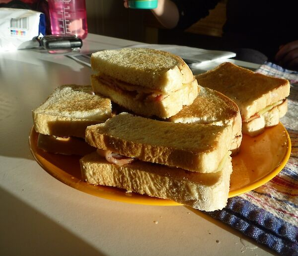 A plate of toasted bacon and cheese sandwiches