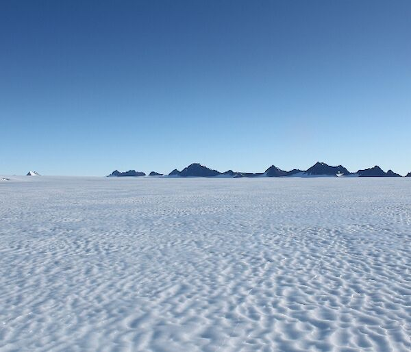 Featureless Ice Plateau with mountain range in distance