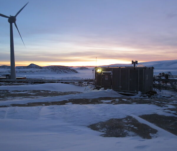 Silver hydroponics hut in foreground with sun rise in background