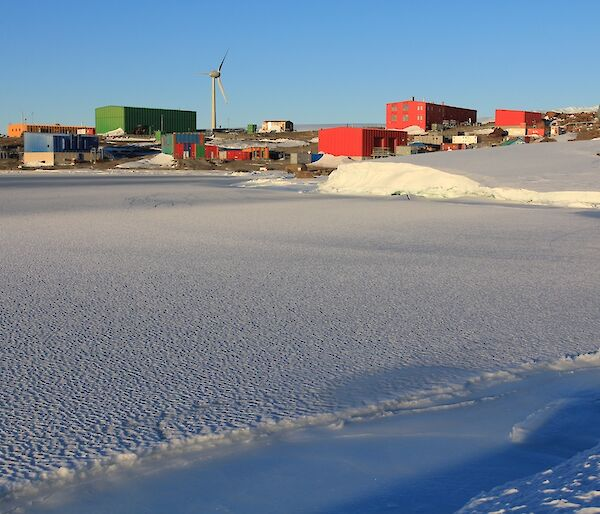 View of Mawson station with sea ice in the foreground.