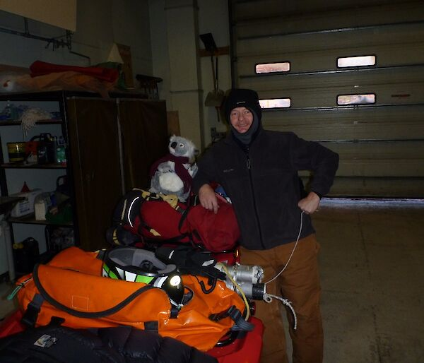 A quad bike prepared for sea-ice travel with a koala named Bear Grylls on the bike and an expedioner standing beside the vehicle