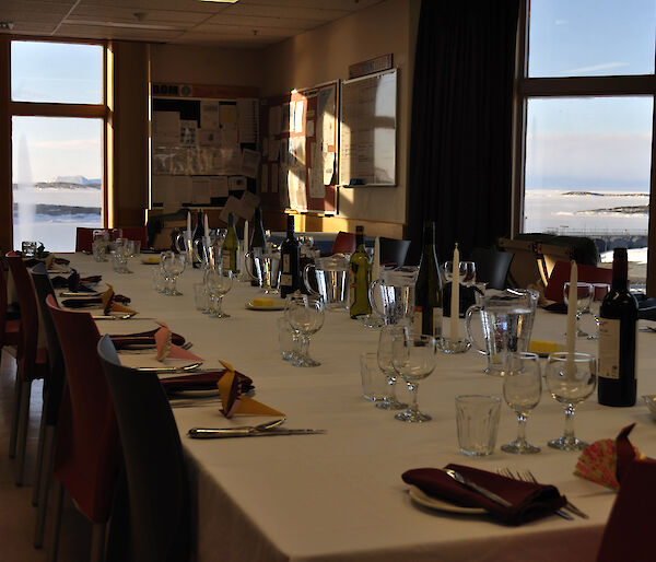 The dinner table set up with individual places and the view through the windows showing sea-ice and icebergs