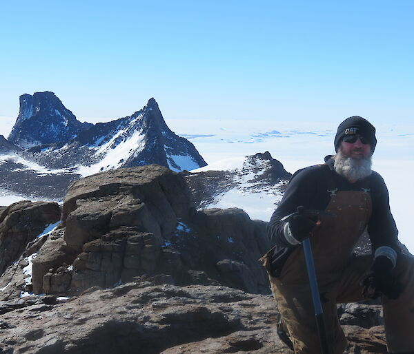 An expeditioner on a rocky platform with the tooth like summit of Fang Peak and another summit behind him