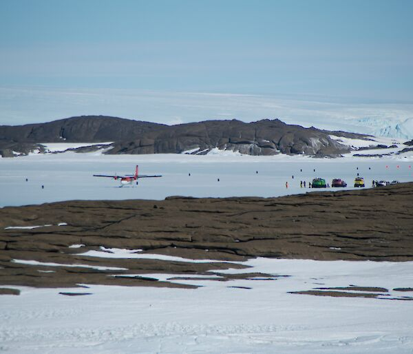 A photo from station across Horseshoe Harbour with a Twin Otter and several vehicles on the sea ice