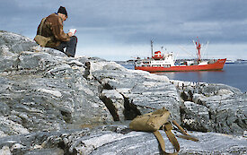 A scientist sits on a rock overlooking a bay writing in his field notebook.