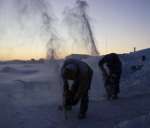 Expeditioners use a chainsaw to cut into the sea ice at Mawson station in preparation for their midwinter swim