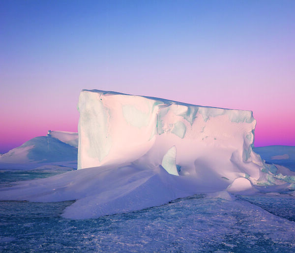 A tabular iceberg against a pink sunset.