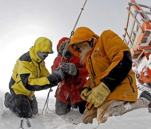 Three expeditioners outdoors gathered around a cable