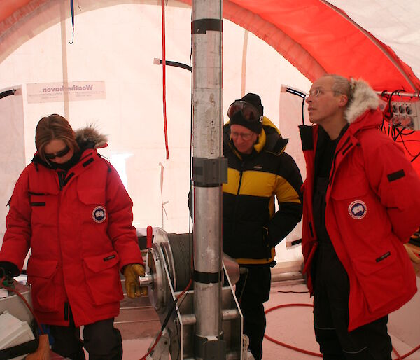 Three Antarctic scientists watch the ice core drill inside a drilling tent at Law Dome.