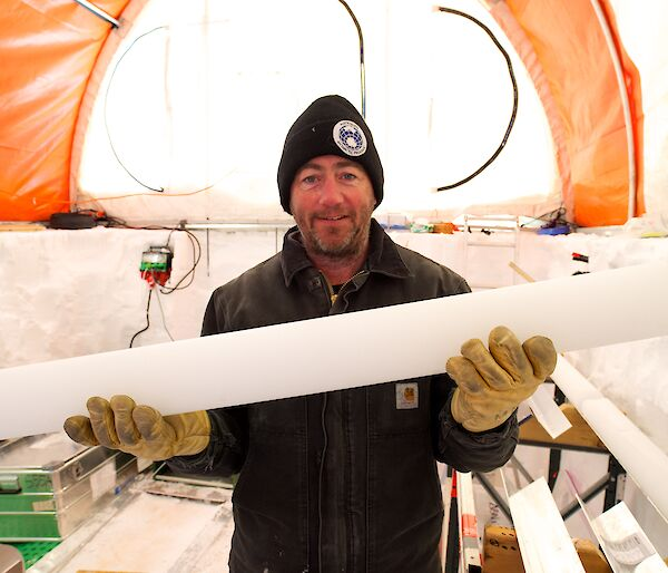 Dr Mark Curran holds up a one-metre length of ice core.