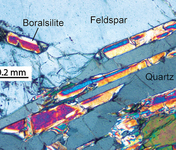 A photomicrograph of brightly coloured crystals of boralsilite