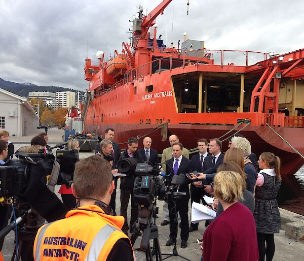 Environment Minister Greg Hunt surrounded by media in front of the orange icebreaker ship Aurora Australis on Hobart's waterfront.