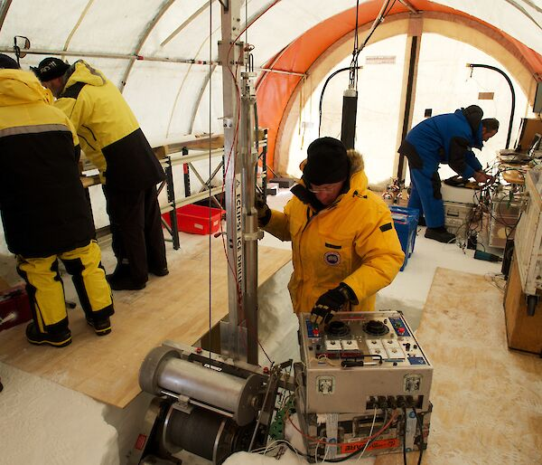 Five scientists in a drill tent with one using the Eclipse drill and others processing ice cores