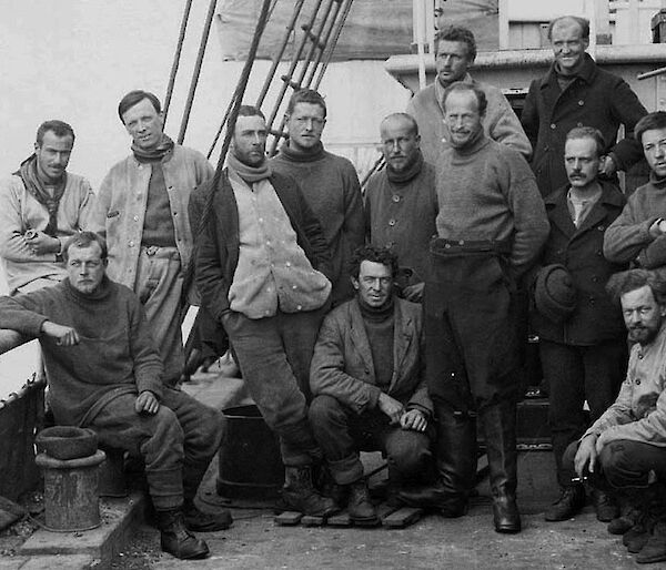 Very old photograph of a group of thirteen men on a ship
