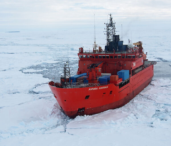 Aerial view of the ship Aurora Australis surrounded by icy and water.