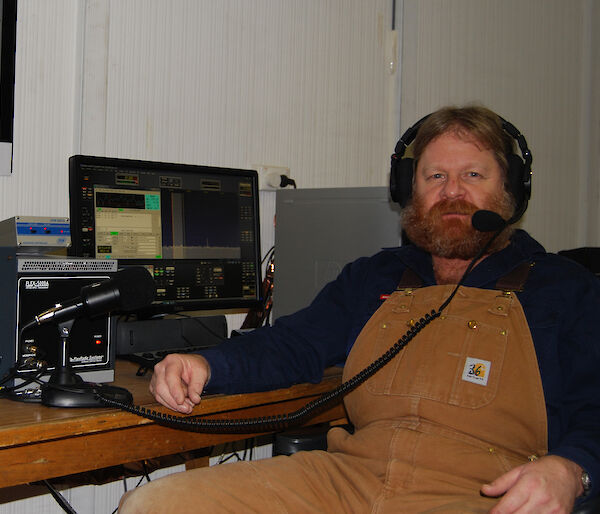 Craig Hayhow sitting in front of his radio at Mawson station.