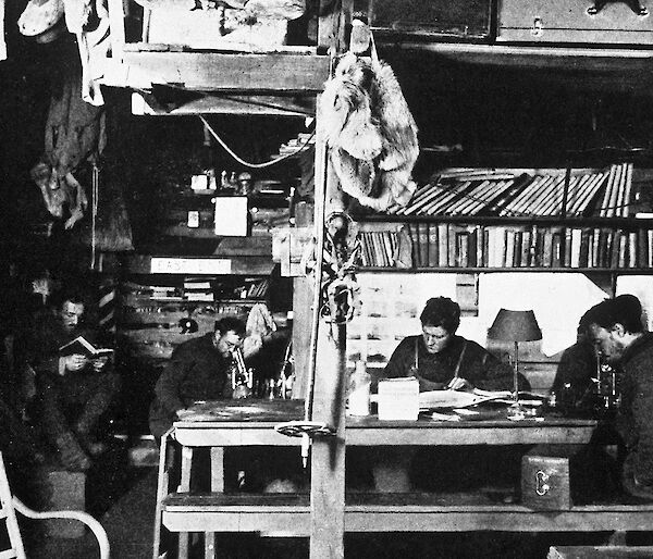 A winter afternoon in the living hut at Commonwealth Bay. (L-R) Dr Xavier Mertz (reading), Archie McLean, Cecil Madigan, and John Hunter.