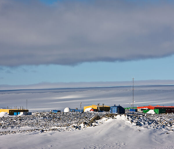 The buildings of Casey station are coloured in reds, yellows and greens and surrounded by ice.