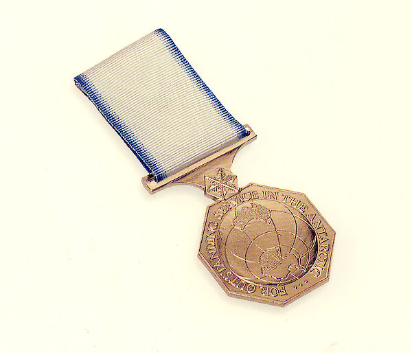This bronze medal shows a map of Antarctica and the words 'For outstanding service in the Antarctic'