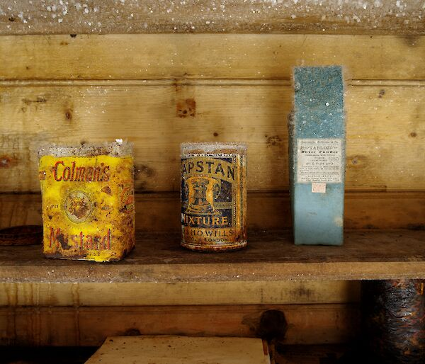 Old tin of mustard and two other original packets on an icy wooden shelf