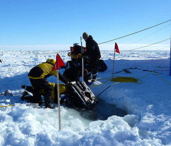 Scientists lower scientific equipment into a hole in the ice.