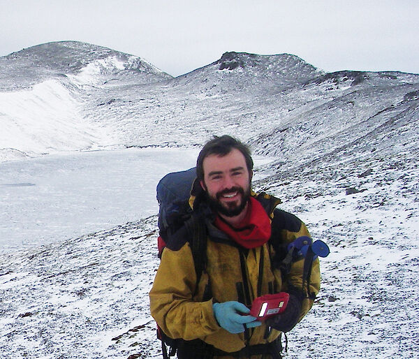 Man smiling at camera surrounded by snow on Macquarie Island.