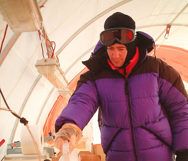 Scientist inspects an ice core in a field drill tent