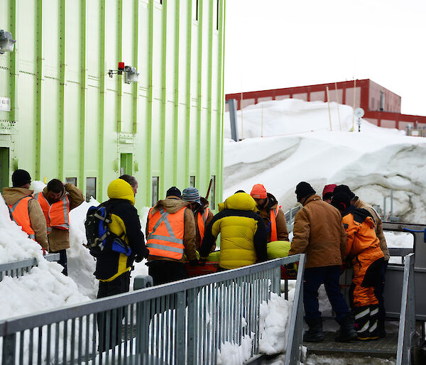 Line of expeditioners pass a stretcher from the building into the back of a Hagglunds vehicle.