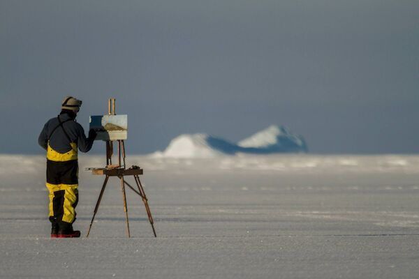 JOhn Kelly wearing protective Antarctica gear, paints with an easel set up on the ice,