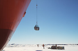 A crane on the Aurora Australia uploads cargo from the ice onto the ship
