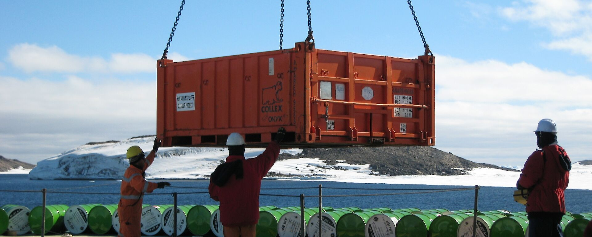 Workers on the Aurora Australis use a crane to unload cargo as part of resupply operations at Davis station