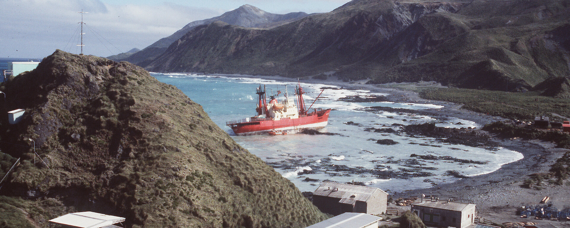 Grounded ship, the Nella Dan, up on rocks near Macquarie Island station buildings