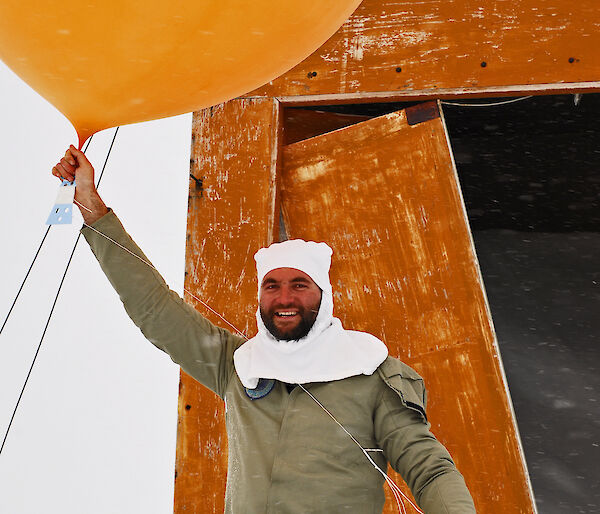 Weather observer holding helium-filled weather balloon