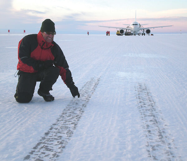Runway Construction Supervisor pointing out tyre marks on the ice runway — A319 in background.