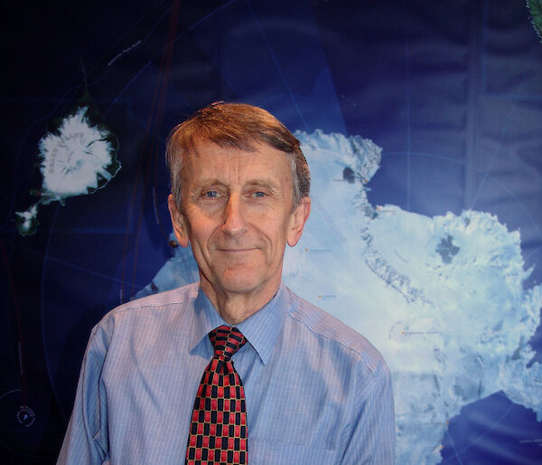 Chief Scientist, Professor Michael Stoddart, poses in front of map of Antarctica