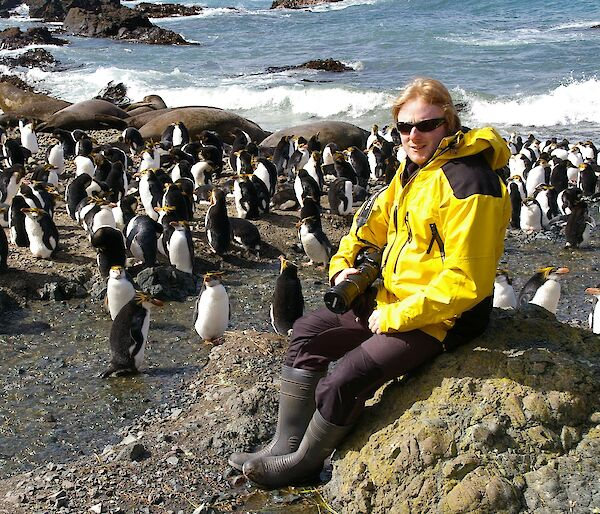 Expeditioner seated on rock with penguins in background