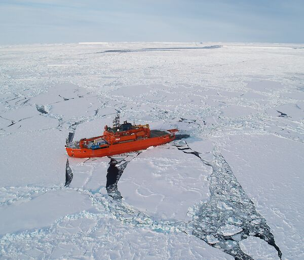 Aerial photo of orange Aurora Australis in pack ice.