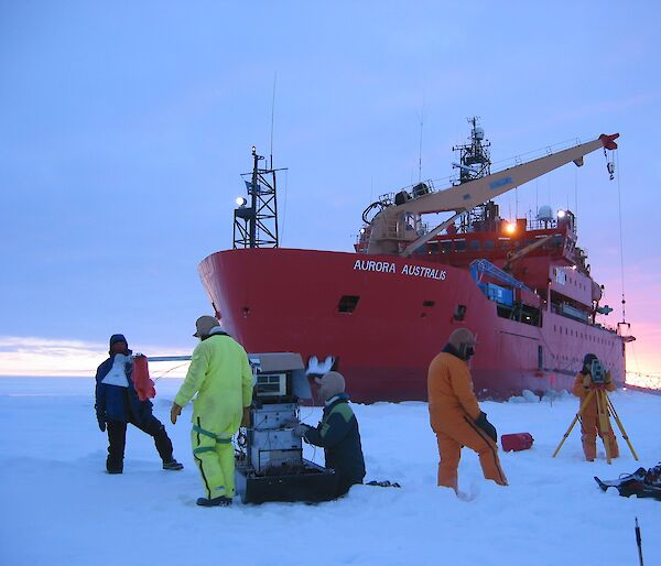 Several scientists working on sea ice in front of the ice breaker, Aurora Australis.
