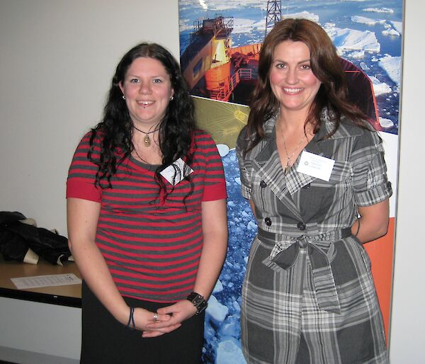Two female teachers stand in front of a poster of the research vessel, Aurora Australis.