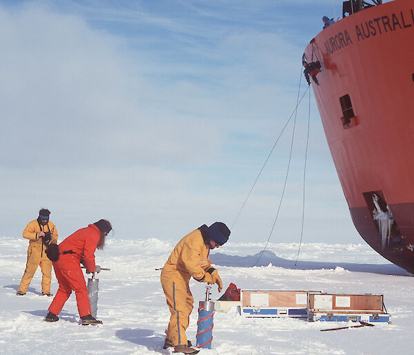Expeditioners undertaking ice coring, with icebreaker ship in background