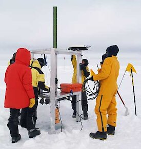 Five people working on sea ice to set up equipment.